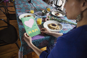 High angle view of woman holding greeting card on birthday at dining table