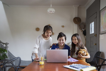 Happy family looking at laptop on table at home