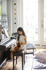 Girl sitting with teddy bear by piano at home