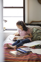 Teenage girl studying with headphones on bed at home
