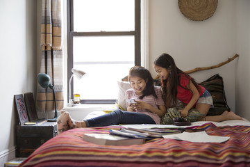Happy sisters using smart phone on bed at home