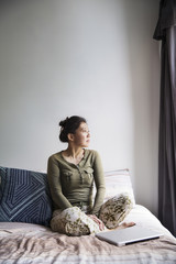 Thoughtful woman sitting with laptop on bed at home