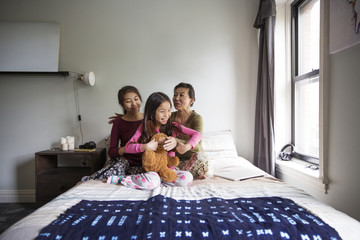 Mother playing with daughters on bed at home