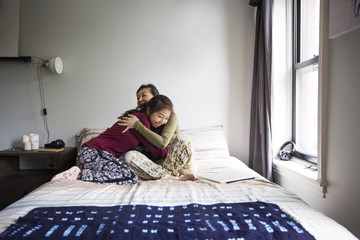 Mother embracing girl while sitting on bed at home