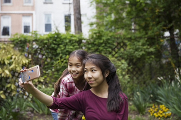 Happy sisters taking selfie through phone while sitting against plants in city