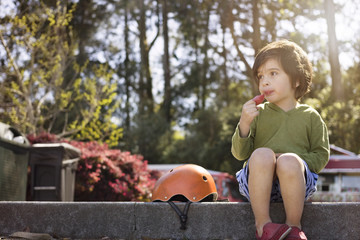 Thoughtful boy eating watermelon at park