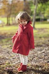 Cute girl in red jacket standing on field