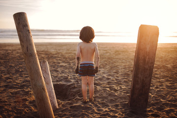 Rear view of shirtless boy standing on beach during summer
