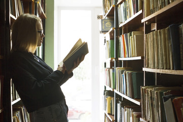 Woman reading book while standing in library