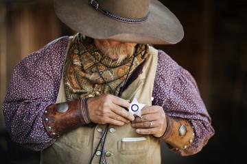 Senior male cowboy wearing star shaped badge at stable