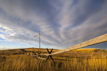 Windmills and wooden fence on field against cloudy sky