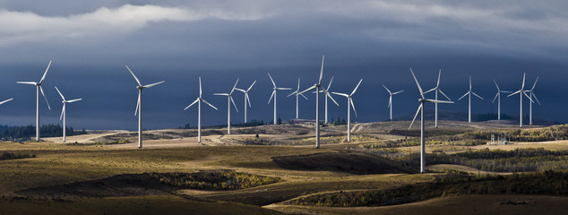 Windmills on landscape against cloudy sky