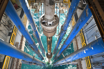 High angle view of drilling riser and pipes in sea at oil rig