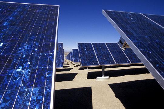 Solar panels on field against clear blue sky