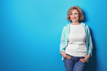 Portrait of beautiful middle-aged woman on blue background Wall mural
