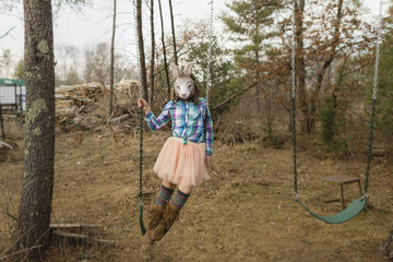 Playful girl in rabbit mask swinging in backyard