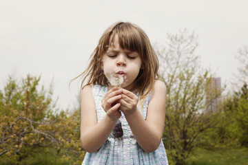 Cute girl blowing dandelion on field against clear sky