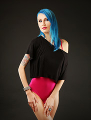 Beautiful young woman with stylish color hair and tattoo on dark background