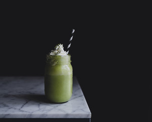 Close up of matcha shake on marble counter against black background