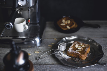 High angle view of French toasts with almonds served in plate by espresso maker on wooden table