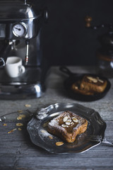 French toasts with almonds served in plate by espresso maker on wooden table