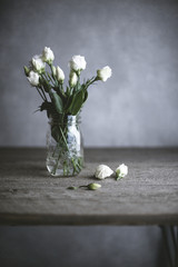 White roses in jar on wooden table
