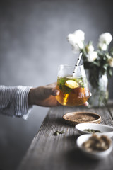 Cropped image of woman holding golden mojito