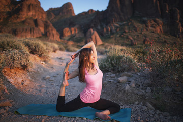 Woman practicing One-Legged King Pigeon Pose on field against mountains