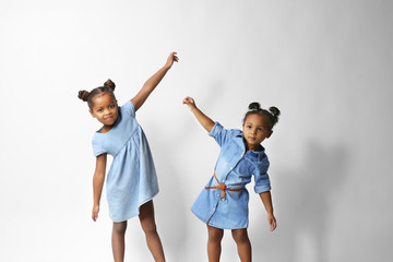 Two cute dancing African girls on white background