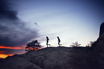 Silhouette couple running on hill against sky during sunset