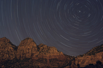 View of mountains against star trails at night