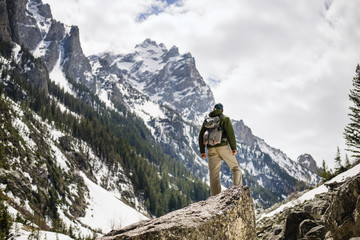 Rear view of hiker standing on rock against snowcapped mountain