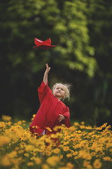 Girl wearing graduation gown throwing cap standing amidst yellow flowers on field