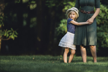 Thoughtful girl with mother standing on grassy field