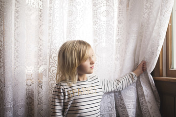 Thoughtful girl standing against curtain looking through window