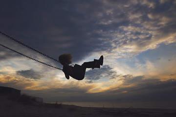Side view of girl playing on swing at beach against cloudy sky during sunset