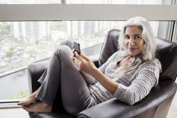 Woman holding smartphone while sitting on chair at home