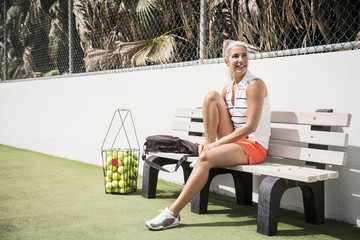 Full length of smiling mature woman sitting at tennis court