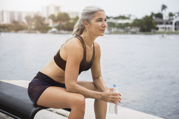 Thoughtful sporty woman holding water bottle while sitting on bench by river