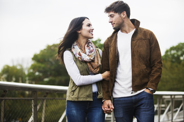 Loving couple looking at each other while walking on bridge