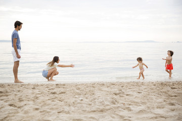 Happy family enjoying at beach against sky