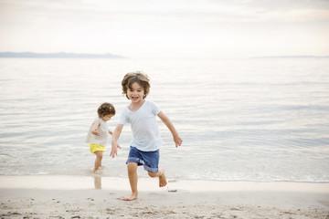 Happy siblings playing at beach against sky