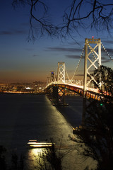 Illuminated Oakland Bay Bridge over sea at night
