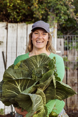 Portrait of happy farmer holding leaf vegetables at field