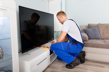 Male Electrician Fixing Television