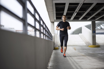 Determined male athlete running in parking lot