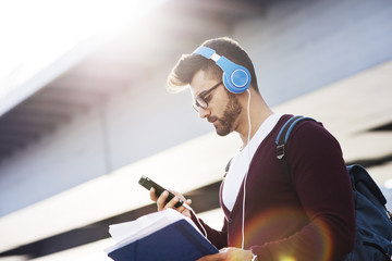 Young man using phone while listening music against bridge