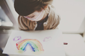Cute girl looking at rainbow painted on paper