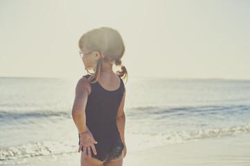 Rear view of girl in swimwear standing on beach