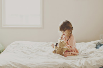 Cute girl playing with teddy bear on bed